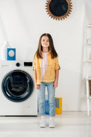 Photo for Child in yellow shirt and jeans standing in laundry room - Royalty Free Image