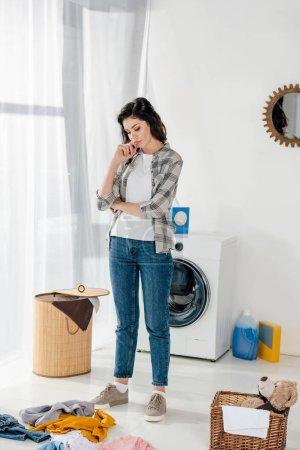 Photo pour Femme debout près de paniers et de regarder à vêtements épars sur le plancher de salle de lavage - image libre de droit