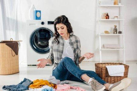 Photo pour Confus femme assise sur le plancher près de vêtements épars et des paniers dans buanderie - image libre de droit