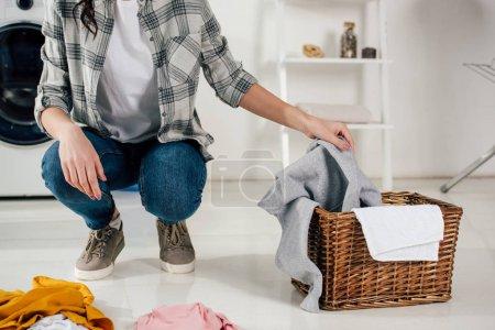 Foto de Recortar vista de poner ropa de mujer a la cesta de lavadero - Imagen libre de derechos