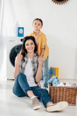 Photo for Daughter in yellow shirt holding mother sitting on floor near basket in laundry room - Royalty Free Image
