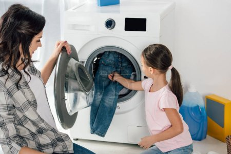 daughter in pink t-shirt and mother putting clothes in washer in laundry room
