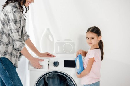 daughter in pink t-shirt holding washing powder wile mother opening washer in laundry room