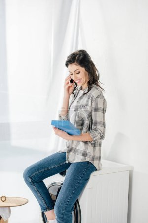 Photo pour Femme assise sur la machine à laver, parler sur smartphone et tenant la lessive dans la buanderie - image libre de droit