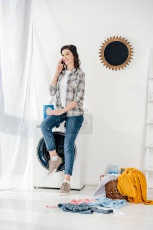 Photo pour Femme en chemise grise et jeans, assis sur la machine à laver et parler au smartphone dans buanderie - image libre de droit
