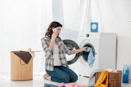 Photo pour Femme mettant les vêtements dans la laveuse et parler au smartphone dans buanderie - image libre de droit
