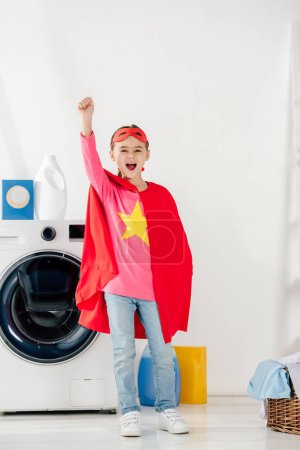 Photo for Child standing in red homemade suit with star sign and showing celebrating in laundry room - Royalty Free Image