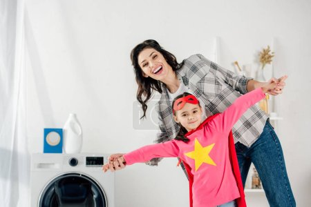 mother in grey shirt and daughter in red homemade suit with star sign having fun in laundry room