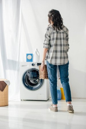 back view of woman in grey shirt and jeans holding basket near washer in laundry room