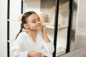selective focus child in white bathrobe looking to mirror and applying cosmetic cream in bathroom