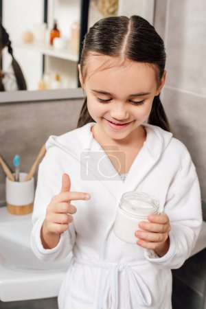 Photo for Child in white bathrobe holding container with cosmetic cream in bathroom - Royalty Free Image