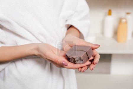 Photo pour Vue recadrée en peignoir blanc de femme tenant du savon dans la salle de bain - image libre de droit