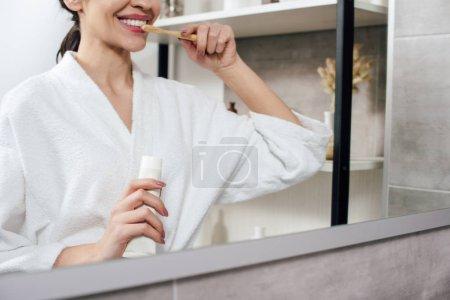 Photo pour Recadrée vue de femme en peignoir blanc se brosser les dents et j'ai de miroir dans la salle de bain - image libre de droit
