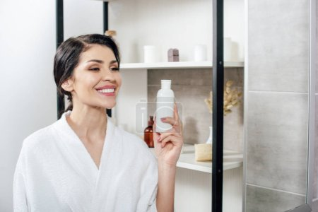 Photo for Woman in white bathrobe looking to mirror, holding bottle with lotion and smiling in bathroom - Royalty Free Image