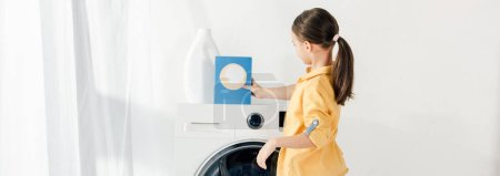 panoramic shot of child standing near washer and putting washing powder in laundry room