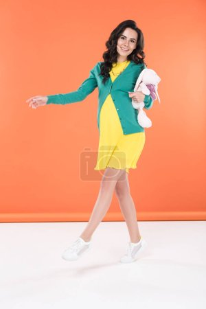 Photo for Carefree brunette pregnant young woman holding toy on orange background - Royalty Free Image