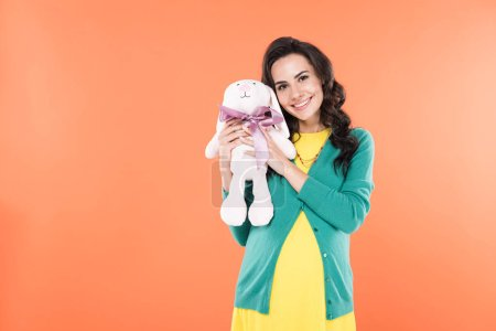 Glad curly pregnant woman holding toy rabbit isolated on orange