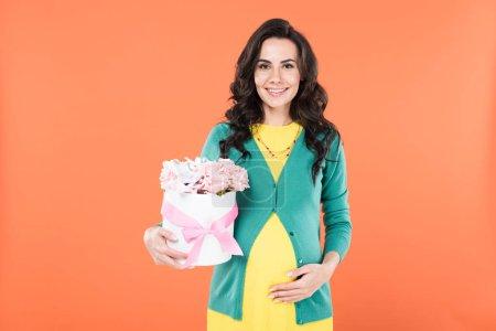Photo pour Jolie femme enceinte tenant des fleurs roses et toucher le ventre isolé sur orange - image libre de droit