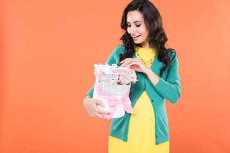 Photo pour Femme enceinte brune excitée toucher fleurs isolées sur orange - image libre de droit