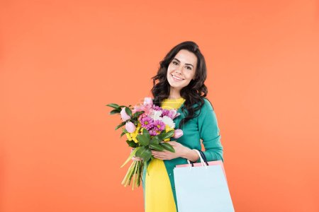 Photo for Curly pregnant woman holding flower bouquet and shopping bags isolated on orange - Royalty Free Image
