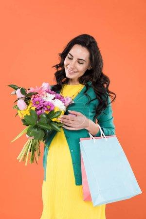 Photo pour Heureuse femme enceinte avec des sacs à provisions en regardant les fleurs avec smile isolés sur orange - image libre de droit