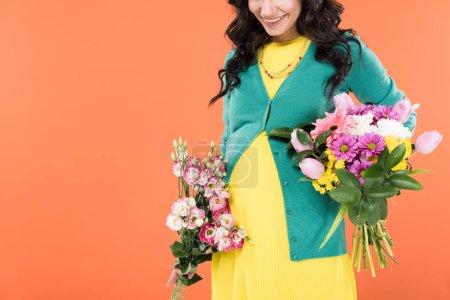 Foto de Vista recortada de alegre mujer embarazada con Ramos de flores aisladas en naranja - Imagen libre de derechos