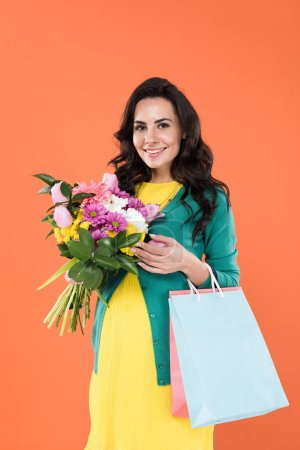 Photo for Joyful pregnant woman with shopping bags holding flower bouquet isolated on orange - Royalty Free Image