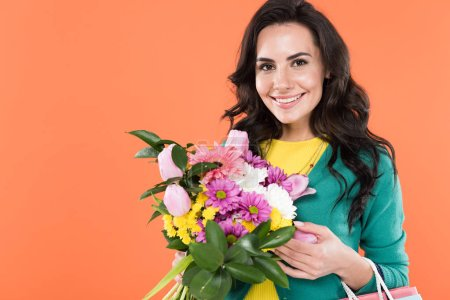 Photo for Attractive curly woman holding flowers and smiling isolated on orange - Royalty Free Image