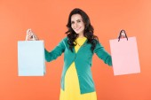 Charming pregnant woman holding shopping bags and smiling isolated on orange