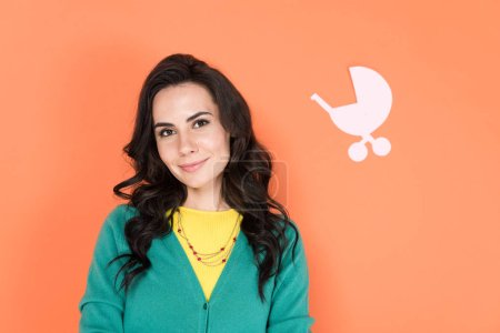 Photo for Charming curly woman in green cardigan isolated on orange - Royalty Free Image
