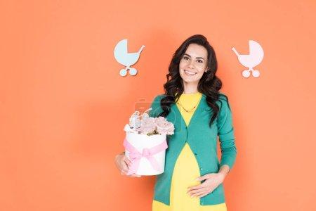 Photo pour Charmante femme enceinte de cardigan vert tenant des fleurs sur fond orange - image libre de droit