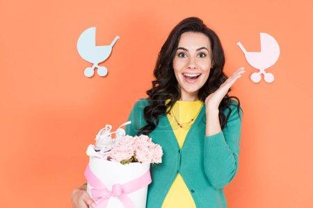 Photo pour Femme enceinte étonnée, tenant des fleurs roses sur fond orange - image libre de droit