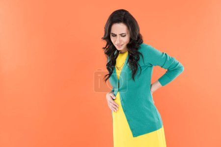 Photo for Upset pregnant woman suffering from back pain isolated on orange - Royalty Free Image