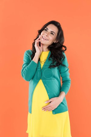 Photo for Stunning pregnant woman in bright clothes looking up with smile isolated on orange - Royalty Free Image