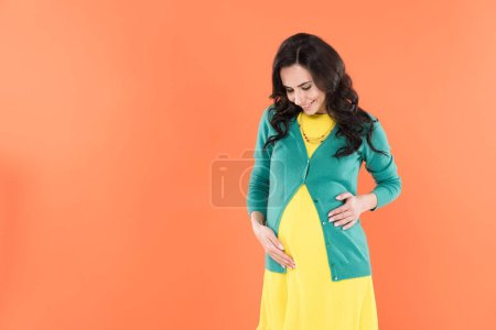 Photo for Blissful pregnant woman in bright clothes touching belly isolated on orange - Royalty Free Image