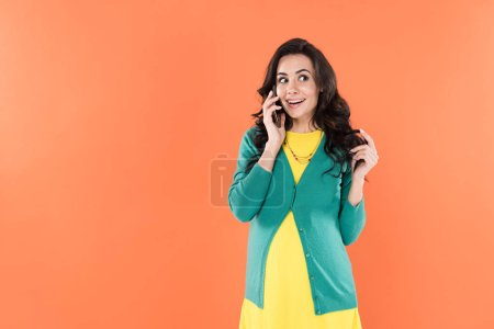 Photo for Joyful pregnant woman talking on smartphone and playing with curly hair isolated on orange - Royalty Free Image