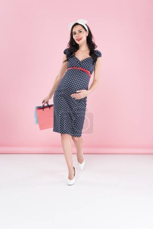 Photo for Amazing pregnant woman in dotted dress holding shopping bags on pink background - Royalty Free Image