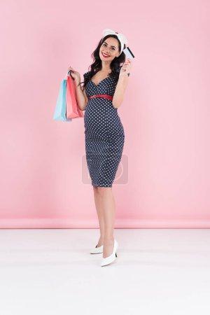 Mujer embarazada dichosa en vestido punteado sosteniendo bolsas de compras y tarjeta de crédito sobre fondo rosa