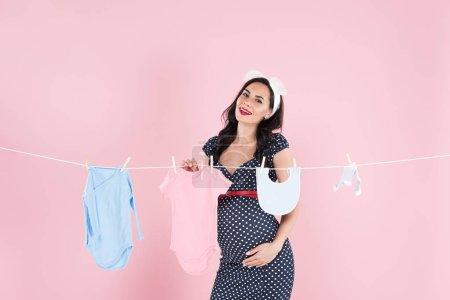 Photo pour Femme enceinte en robe pointillé traîner les vêtements de bébé sur la corde à linge sur fond rose - image libre de droit