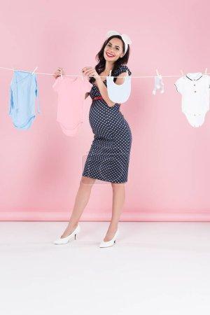 Photo pour Vue sur toute la longueur heureuse femme enceinte traîner les vêtements de bébé sur fond rose - image libre de droit