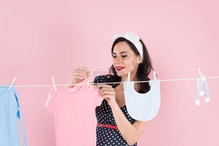 Photo pour Charmante femme enceinte traîner les vêtements pour bébés sur corde à linge isolé sur Rose - image libre de droit