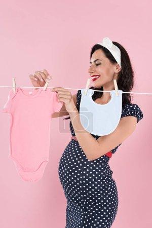 Photo pour Sourire de femme enceinte en robe à pois traîner les vêtements pour bébés sur corde à linge isolé sur Rose - image libre de droit