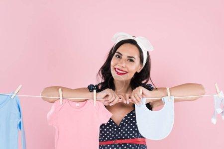 Photo pour Jolie brunette jeune femme traîner les vêtements pour bébés sur corde à linge isolé sur Rose - image libre de droit