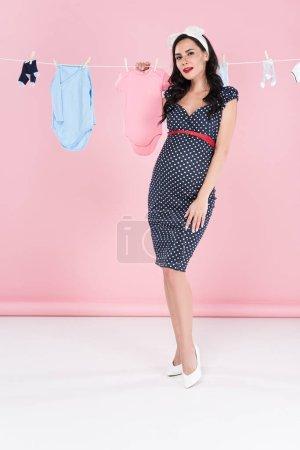 Photo pour Femme enceinte chic en robe traîner les vêtements de bébé sur la corde à linge sur fond rose - image libre de droit