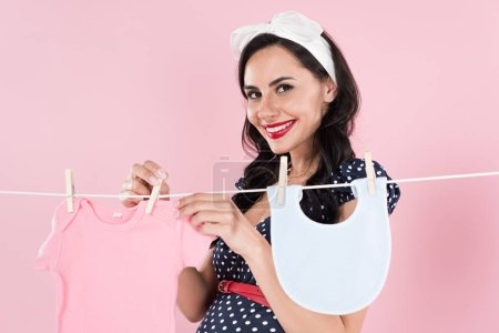 Photo pour Heureuse femme enceinte traîner les vêtements de bébé avec sourire sur fond rose - image libre de droit