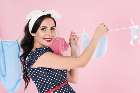 Photo pour Charmante femme enceinte traîner les vêtements de bébé avec sourire isolé sur pink - image libre de droit