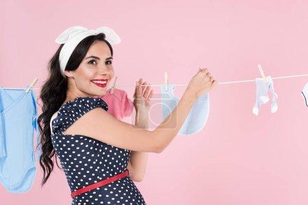 Photo pour Femme enceinte excitée, traîner les vêtements de bébé sur corde à linge isolé sur pink - image libre de droit