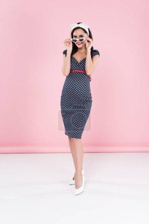 Photo pour Bonne humeur femme enceinte en robe en pointillé qui décollait lunettes de soleil sur fond rose - image libre de droit