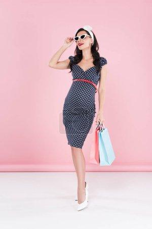 Foto de Elegante mujer embarazada en gafas de sol con bolsas en fondo rosa - Imagen libre de derechos