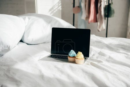 sweet and tasty cupcakes on laptop with blank screen in bedroom